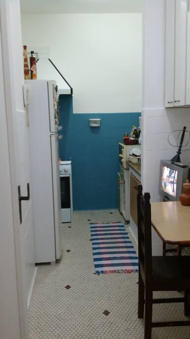 Cozinha com fogão, geladeira, mesa, microondas, armários e TV. Café da Manhã à combinar.