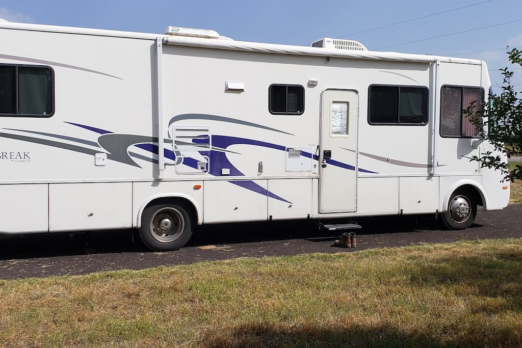 This RV is just an example to give you a sense of scale.  You must provide your own vehicle / tent / rv.