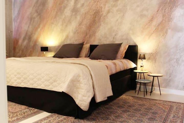 ruime slaapkamer met kastenwand.