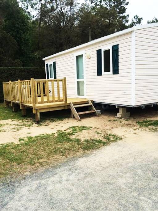 Mobile-Home avec terrasse en bois équipé d'une table de jardins avec 6 chaises et un parasol