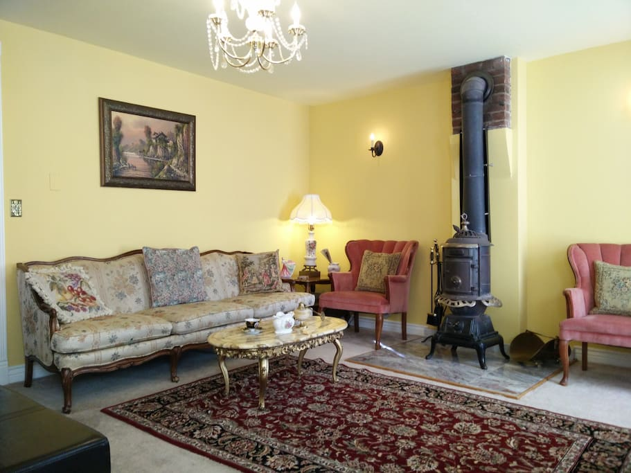 LIVING ROOM HAS A BIG FLAT SCREEN TV AND AN ANTIQUE ORIGINAL FIRE PLACE