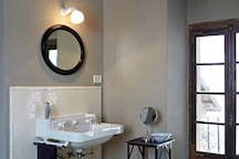 guest bathroom. The bathroom has two sinks, a shower and a bathtub. The French window opens onto a balcony.