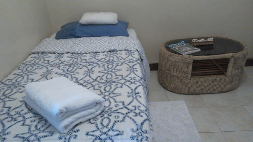 Comfy bed with luxurious towels & palm side table.