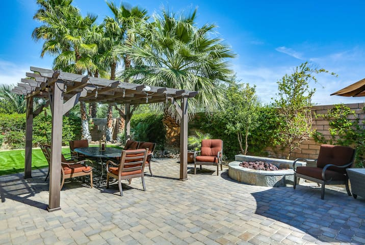 The backyard patio boasts a pergola strung with twinkling lights as well as a fire pit.