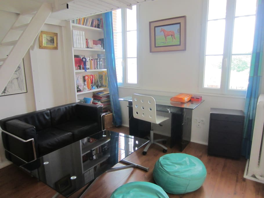 Coin salon avec une table basse qui peut monter et devenir une table à manger.