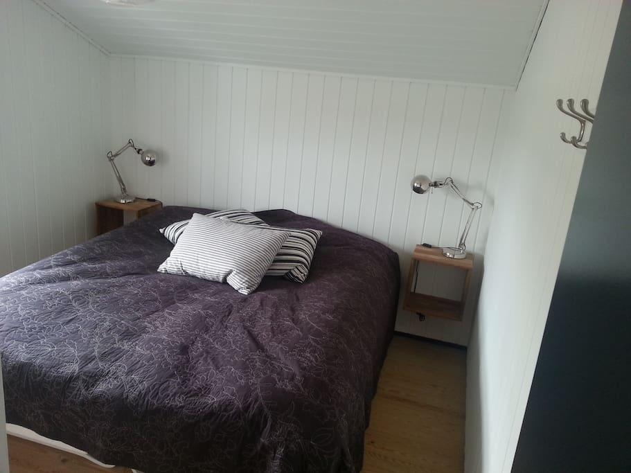 Rummeligt soveværelse med indbygningsskabe.