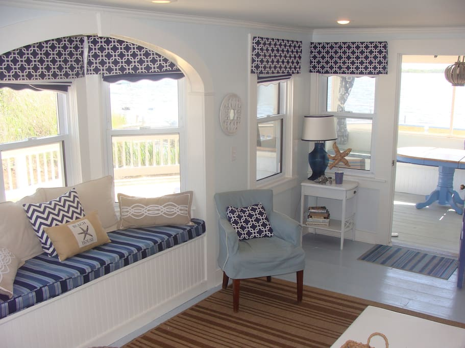Living room with window seat.  Opens up to screen in porch with cushioned bench and table.