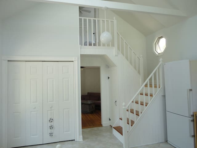 Vaulted ceiling eat-in-kitchen facing living room and staircase to upper bedroom.