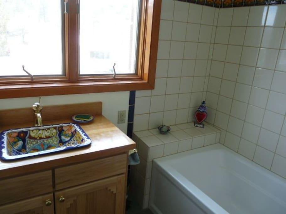 full bathroom contains talavara sink and Mexican tiles