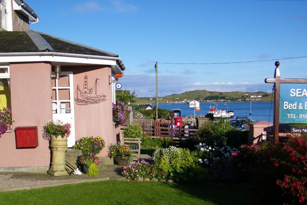 Summer front garden at Seaview with views down to the ferry and across to Iona.