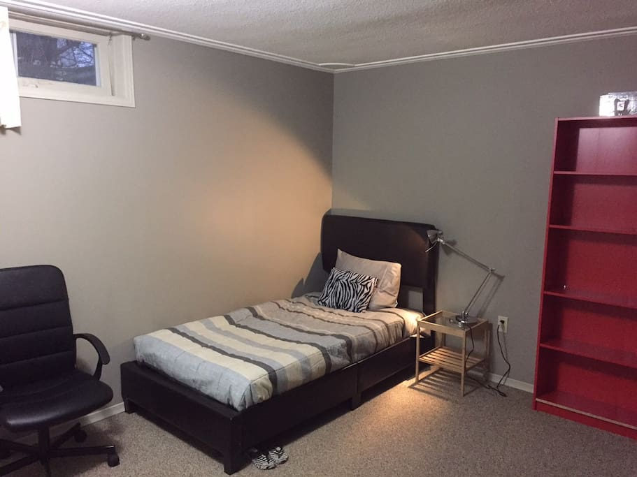 single bed, storage shelf, chair, night table and light are in room