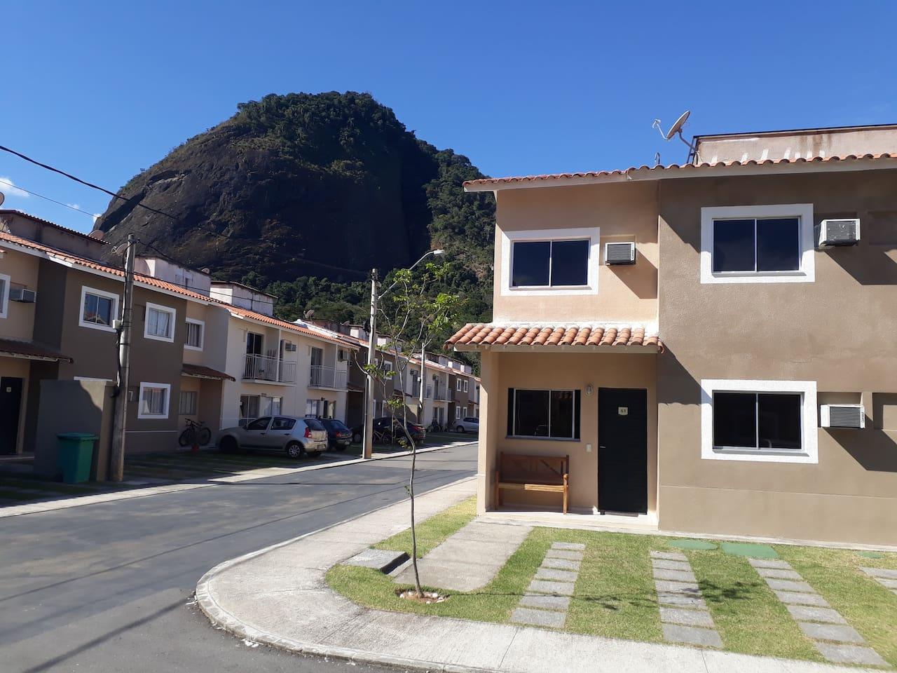 Fachada da casa, rua do condomínio e a Pedra da Liberdade ao fundo, chamada entre os moradores de Pão de Açúcar de Mangaratiba.