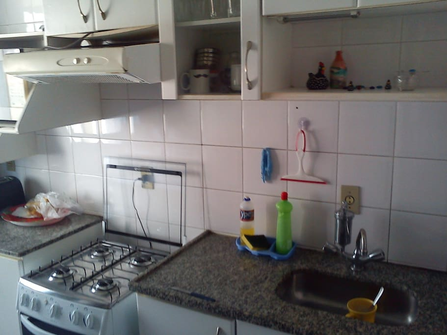 kitchen with stove, microwave, refrigerator and all the utensils to cook.