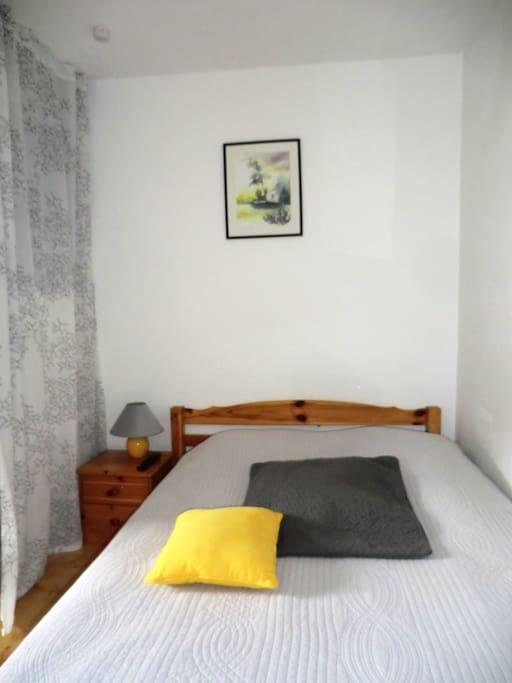 Coin chambre avec lit double et étagères