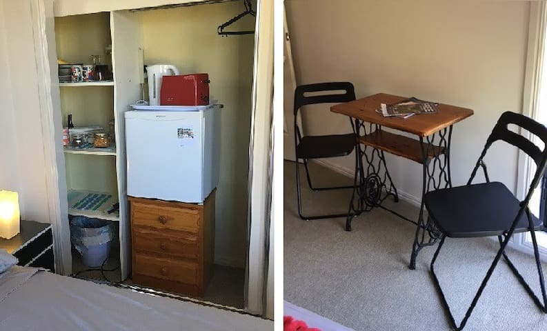 Basic cooking, fridge + table & chairs / workspace in room.