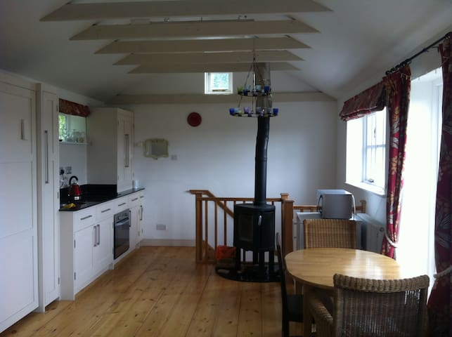 View one end of upstairs studio with woodburning stove and kitchen on the left