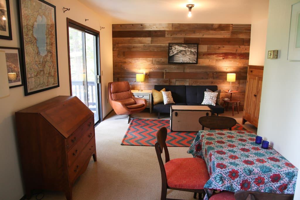 The living room has a small couch, cable TV, an eat-in area and a desk.