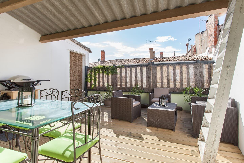 Terrasse avec coin salon, table et 6 chaises, barbecue au gaz Weber