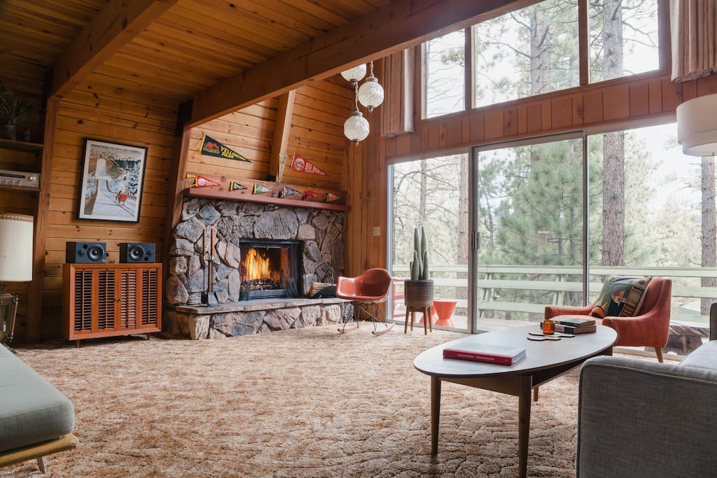 The living room is large and open with so much room for activities. The two story wall of windows looks out into the trees. It's not called Treehouse Vibes for nothing.
