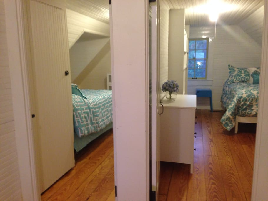 View from stairwell landing- two furnished bedrooms with closets