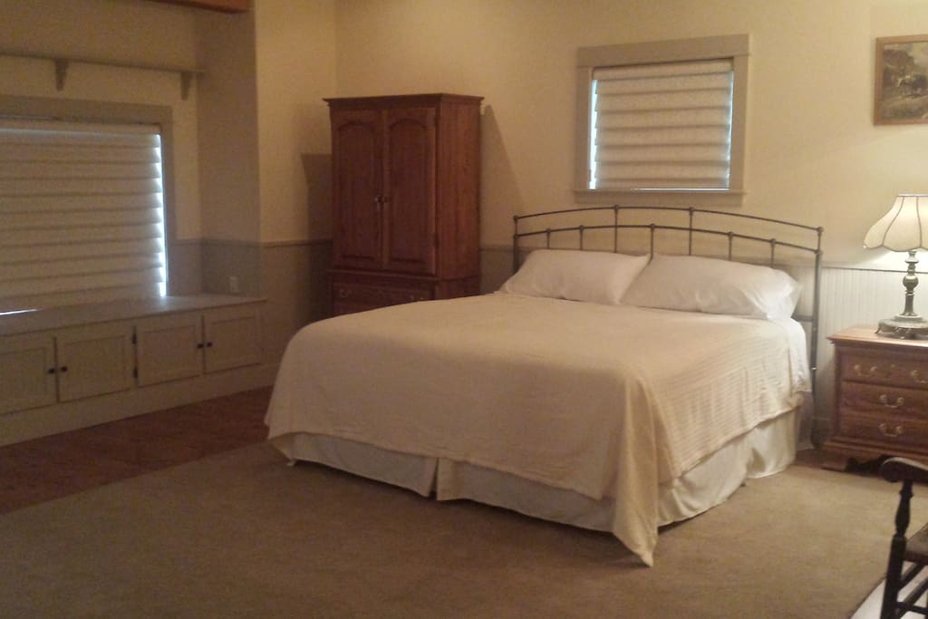 Sleeping area with king bed and highboy chest of drawers with plenty of clothes storage.