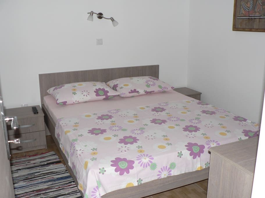 A double bed with colorful crisp sheets