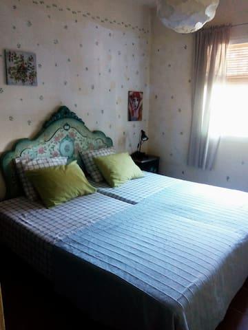 Dormitorio en la planta de abajo con dos camas y gran armario y vistas a la piscina y jardín