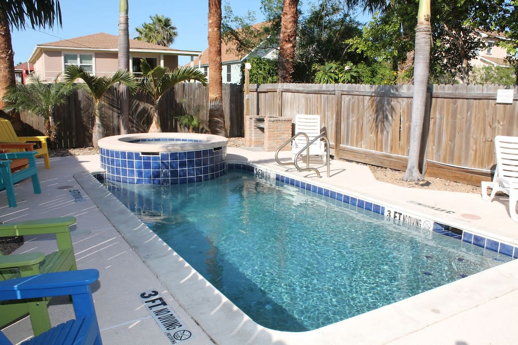 Spacious heated pool area with hot tub.