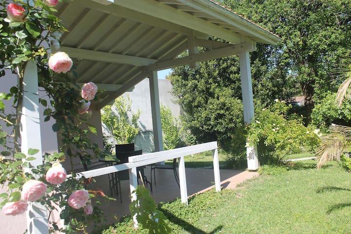 Terrasse couverte équipée d'une table et chaises pour les repas et d'un salon de jardin