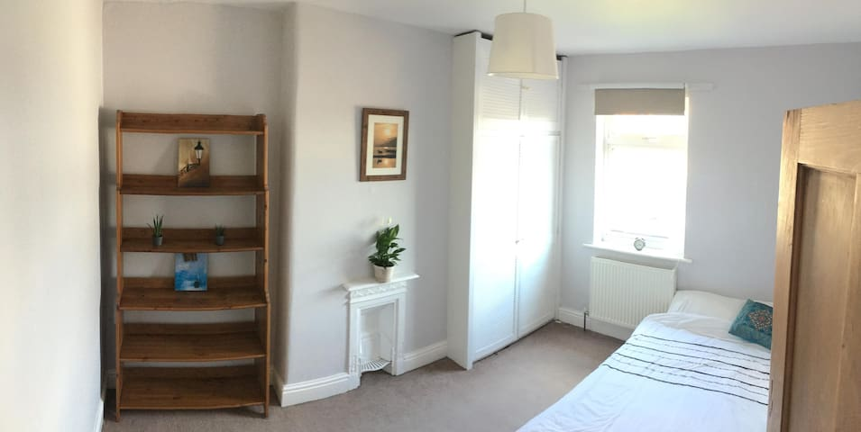 Spacious, bright room, overlooking the garden, with king sized bed (firm) and wardrobe storage.