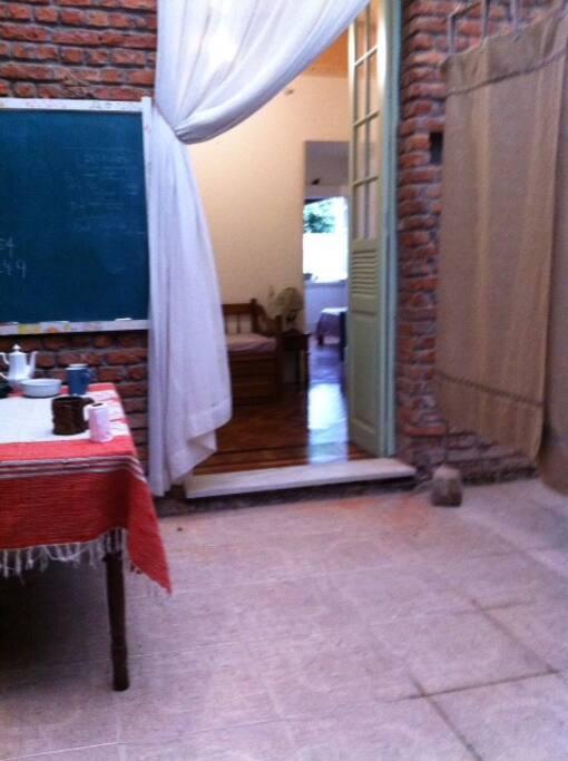 Acesso independente, pátio coberto com banheiro e mesa para o café. Ao fundo, vê-se os 2 quartos.