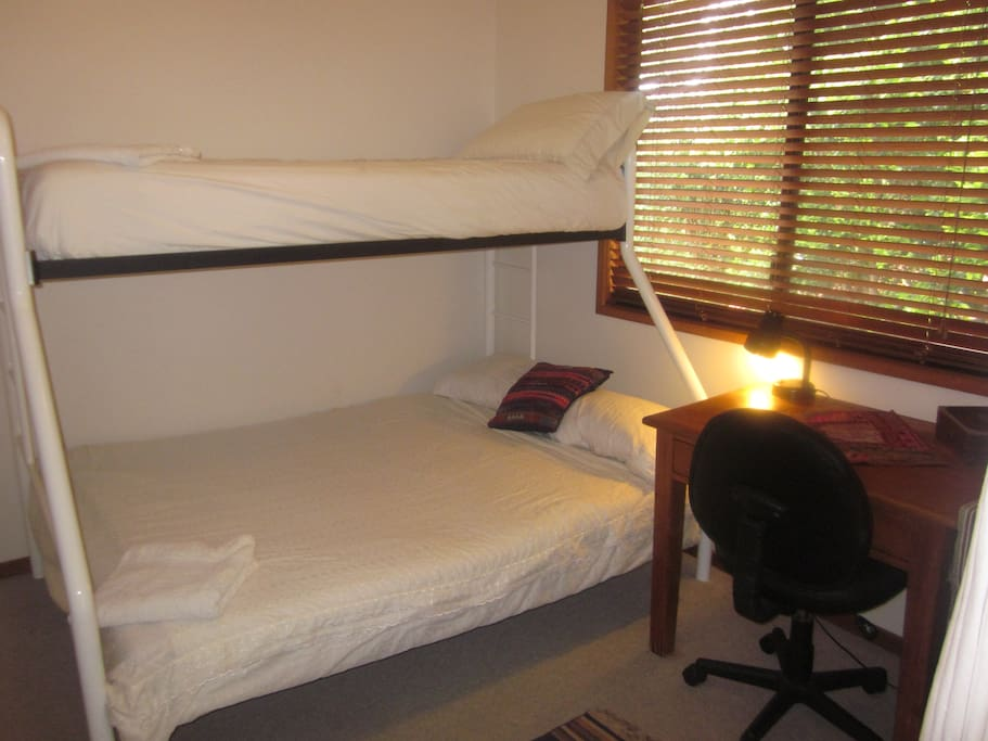 Bunks with a double bed on the bottom.