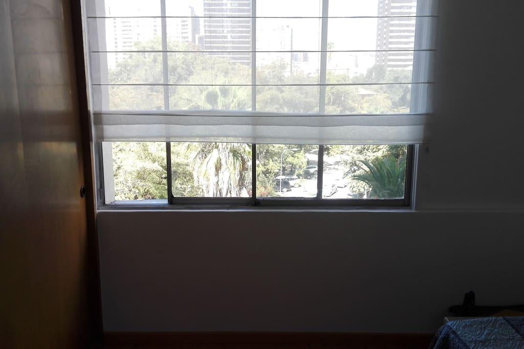 Habitación con ventana y vista al parque.