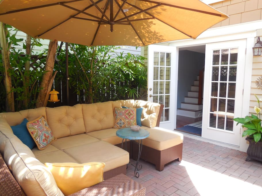 Inside the gated courtyard is an outdoor space with a sofa and table and chairs for outside dining.
