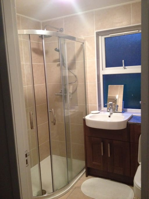 Large modern walk in shower with heated towel rail, vanity basin and toilet.