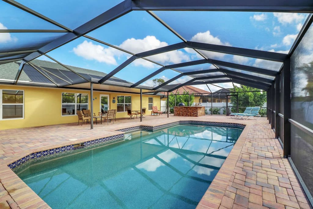 The large solar heated pool is the focal point of this enviable, fully screened, outdoor living space.