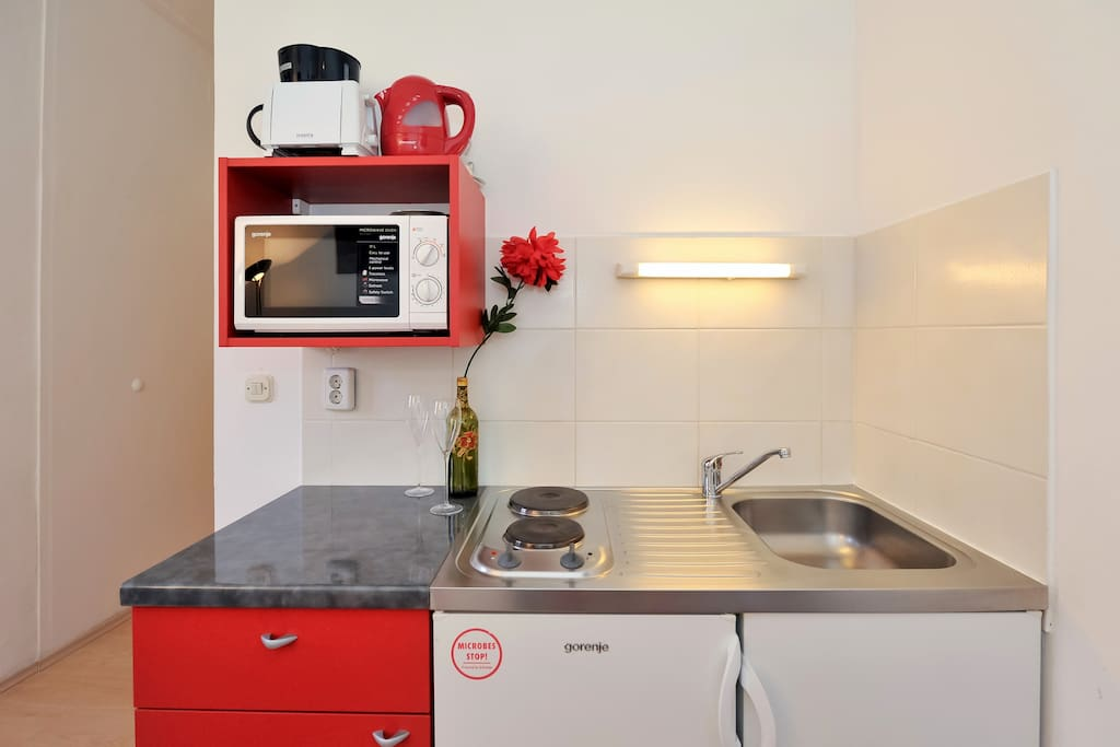 Kitchen with stove, microwave, toaster, kettle, coffee maker, sink and refrigerator