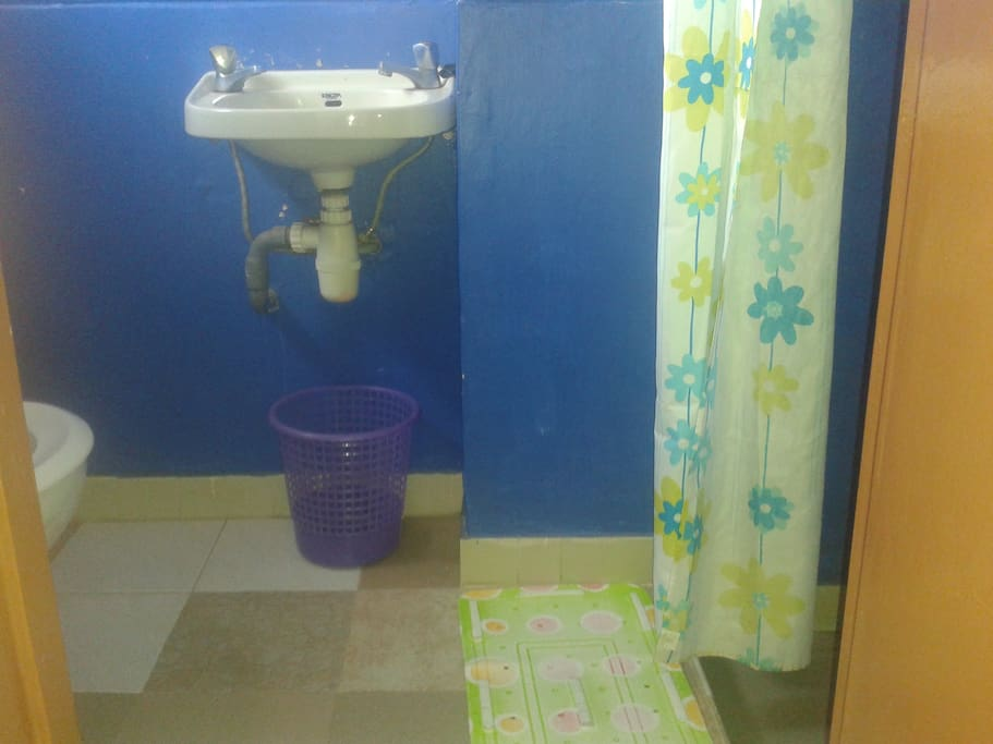 Toilet and bathroom with hot shower.
