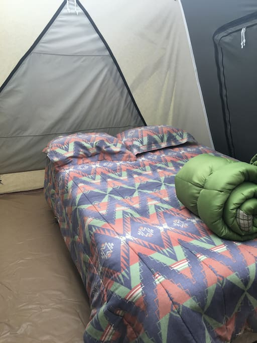 We provide linens, sleeping bags and additional blankets with a full sized bed in the tents.