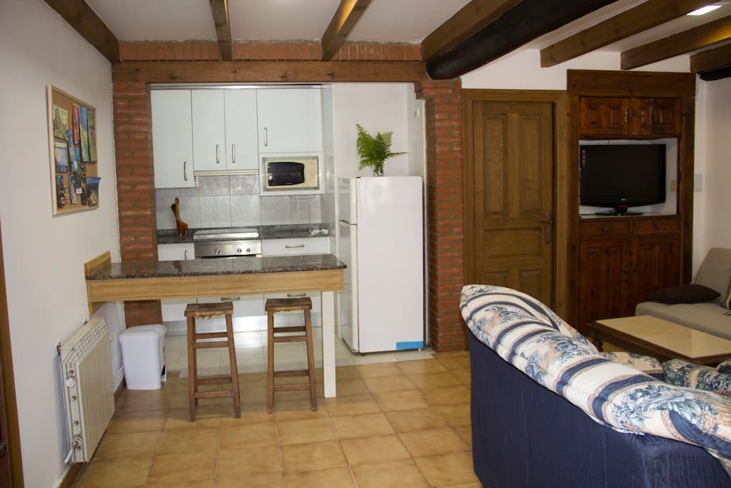 Zona común formada por cocina, sala y comedor. Main area with open kitchen, living room and dining room all together.