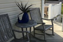 Upper decks with dining table accented by large umbrella and comfortable rocking chairs makes fot pleasant evening dining