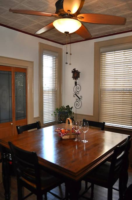 "Formal dining room with triple entry, 2 72"" windows, coat closet, and high-top table that seats 8."