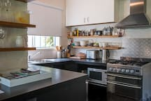 Fully equipped kitchen with gas stove, mini fridge, microwave, kettle & toaster, loads of plates, pans, pots and accessories