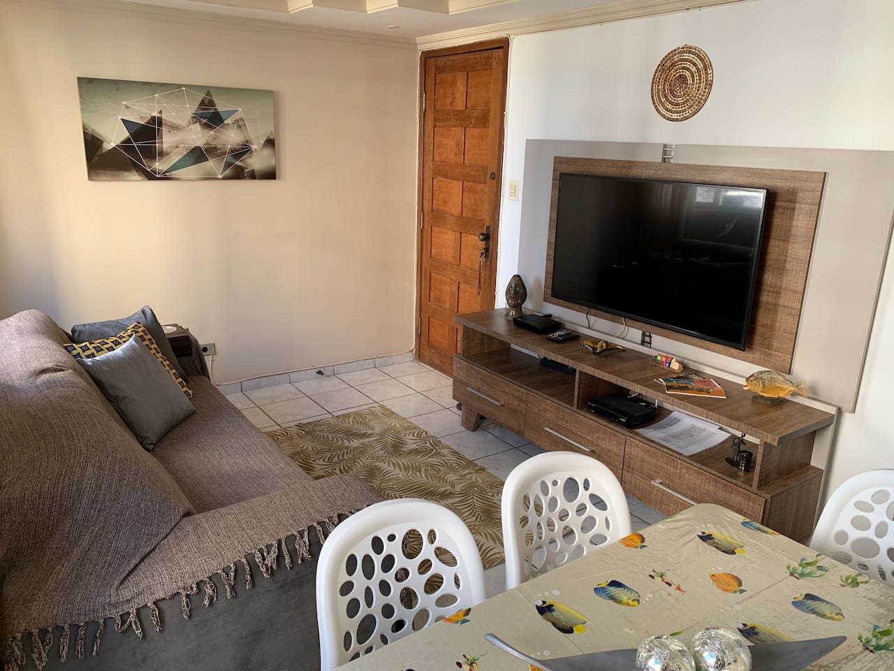 """Sala de estar c/ rack, TV 50"""" c/ NET canais à cabo, WI-FI 35 MB + NETFLIX e sofá-cama retrátil. Decoração c/ almofadas, tapete, mandala, quadros e mini-esculturas."""