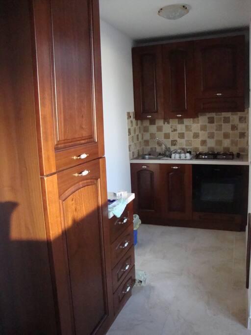 Cucina attrezzata con piano cottura forno, frigo e accessori