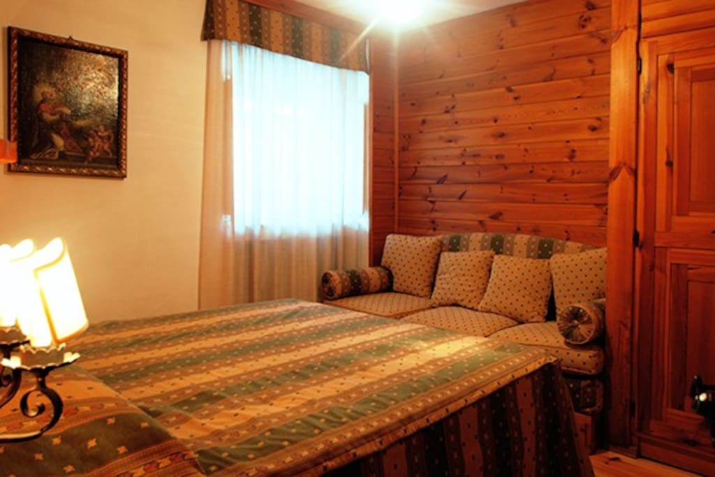 Bedroom 1, with one double bed and one single bed, that you can choose to use as a bed or as a sofa