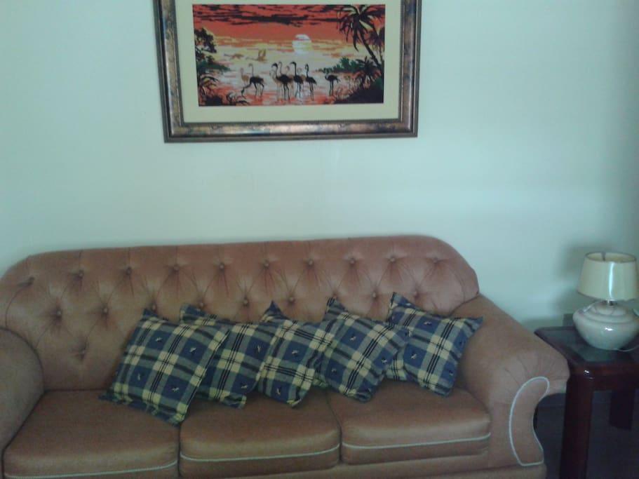 Sala de estar com sofá confortável e TV disponível.