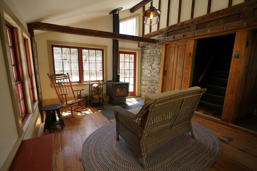 Sitting room off of the kitchen with a wood-burning stove. The best place to relax with a cup of coffee in the morning and see wildlife in the back yard. The French door leads out to a large stone patio.