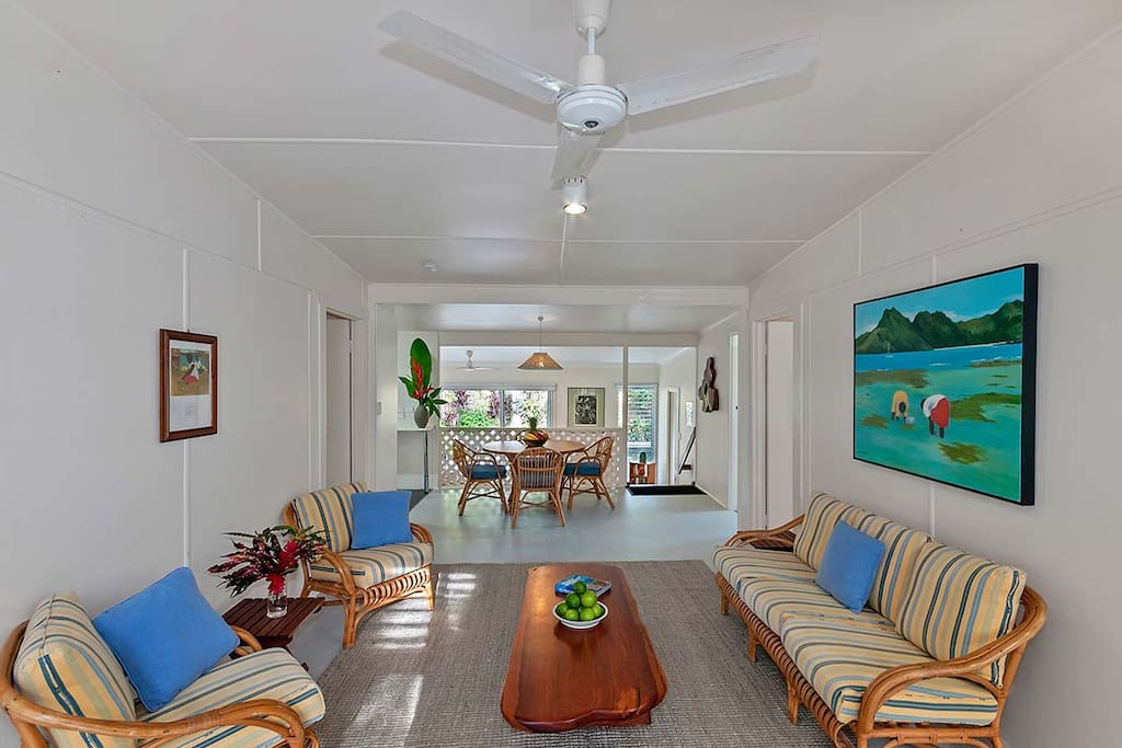 Light filled, spacious living area featuring vibrantly coloured original artwork of life in the tropics by internationally renowned Artist Ray Crooke and his daughter Diana Crooke.