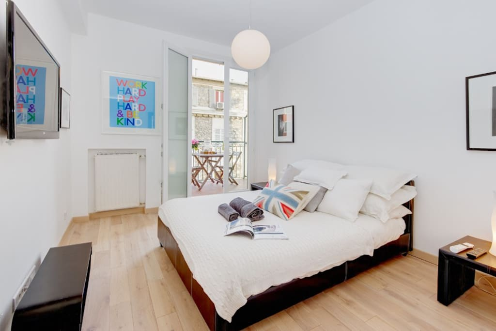 Large bedroom with TV and double bed.
